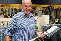 Senior man shopping in garden centre, holding new spade, smiling, portrait