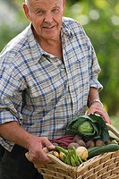 Senior man carrying basket of fresh vegetables from garden, smiling, portrait