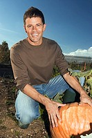 Man kneeling beside large pumpkin in vegetable garden, smiling, portrait