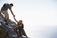 Couple climbing rock in bright sunlight, man assisting woman, side view, sea in background