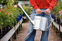 Man carrying watering can in garden centre, front view, mid-section, flowers in background