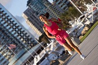 USA, California, San Diego, woman wearing pink sports vest and shorts, jogging, listening to MP3 player strapped to arm, smiling, marina in background...