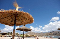 Republic of South Africa, Cape Town, palapa sunshades on sandy beach, resort in background, focus on foreground