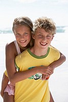 Boy 12-14 carrying girl 12-14 by piggyback on sandy beach, smiling, portrait (thumbnail)