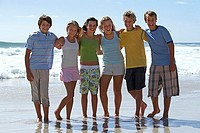Group of teenagers 12-15 standing on sandy beach, side by side, smiling, portrait