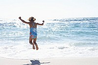 Girl 3-5 wearing swimsuit, jumping above surf on sandy beach, rear view, sea shimmering in sunlight