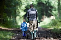 Father and son 2-4 wearing wellington boots, walking along woodland path, side by side, rear view, man pushing baby stroller differential focus