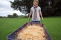 Blonde boy 8-10 wearing colourful striped scarf, holding wheelbarrow full of hay in field, smiling, front view, portrait