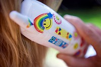 Woman using white mobile phone decorated with smiley face, rainbow and heart shape symbols, close-up, rear view, focus on foreground