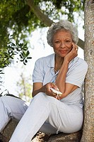 Senior woman sitting in garden, listening to MP3 player, leaning against tree trunk, hand on chin, smiling, portrait