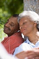 Senior couple listening to MP3 player in garden, sharing earbud headphones, leaning against tree trunk, eyes closed, close-up