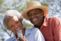 Senior couple reading text message on mobile phone, smiling, man wearing straw hat, close-up tilt