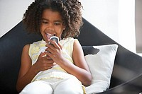 Girl 8-10 sitting in chair at home, reading text message on mobile phone, mouth open, front view