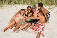 Group of teenagers 13-15 lying on sandy beach, teenage boy taking photograph with camera, smiling (thumbnail)