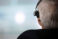 Mature businessman wearing telephone headset, rear view, close-up