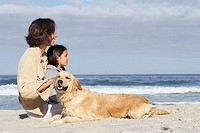 Mother and daughter 6-8 sitting on beach with dog, smiling, side view, sea in background