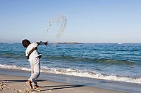 Boy 8-10 throwing sand and stone into sea, standing on beach at water´s edge, rear view