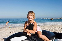 Girl 5-7 sitting on inflatable toy whale on sandy beach, smiling, portrait