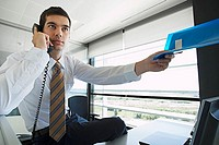 Businessman sitting on desk in office, using telephone, passing blue file