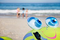 Children 6-10 playing on sandy beach near sea, focus on inflatable toy in foreground