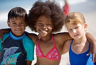 Three children 6-10 standing side by side on beach, smiling, front view, portrait