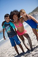 Three children 6-10 standing side by side on beach, smiling, front view, portrait tilt