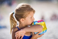 Blonde girl 3-5 blowing air into inflatable armband on beach, side view, close-up