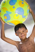 Boy 7-9 standing on beach, holding green beach ball above head, smiling, portrait tilt