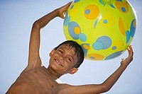 Boy 7-9 holding green beach ball above head, smiling, portrait, upward view, unusual angle