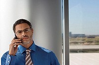 Mature businessman wearing spectacles, using mobile phone beside window, front view