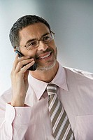 Mature businessman wearing spectacles, using mobile phone behind office partition, smiling, close-up