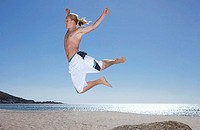 Teenage boy 17-19 in white swimming shorts leaping from rock on beach, side view