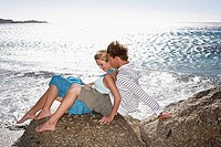 Teenage couple 17-19 sitting on rocky beach in bright sunlight, girl in boy's lap, smiling