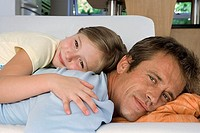 Father and daughter 7-9 lying on sofa at home, smiling, side view, close-up, portrait