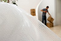 Man sealing box with tape at home, focus on bubble wrap in foreground (thumbnail)
