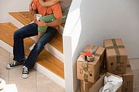Couple sitting at bottom of staircase at home, stack of packed boxes beside wall, low section