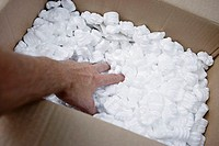 Man filling box with packing foam, rear view, personal perspective, close-up