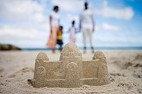 Two generation family standing on beach, focus on sandcastle in foreground, surface level