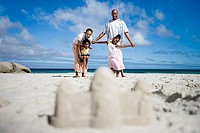 Sandcastle on beach, focus on two generation family in background, portrait, surface level