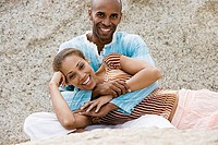 Couple relaxing on rocky beach, woman lying in man's lap, smiling, portrait