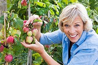 Senior woman holding fruit growing in garden, smiling, close-up, portrait