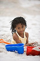 Girl 5-7 playing on sandy beach with bucket and spade, smiling, portrait