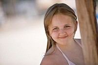 Girl 6-8 standing beneath sunshade on beach, smiling, portrait