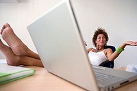 Businesswoman shrugging shoulders, resting bare feet up on desk in office, laptop in foreground
