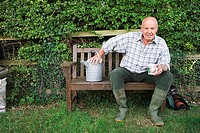 Senior man in wellington boots sitting on bench in garden with mug and watering can, portrait