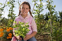 Girl 9-11 holding pot plant in garden, smiling, front view, portrait