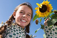 Girl 9-11 standing beside sunflower growing in garden, smiling, close-up, portrait, low angle view