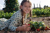 Girl 9-11 lying in beside strawberry plant in garden, smiling, side view, portrait, surface level