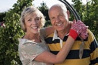 Senior couple standing in garden with arm around each other, smiling, close-up, portrait tilt