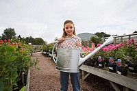 Girl 9-11 standing in garden centre, holding watering can, smiling, portrait